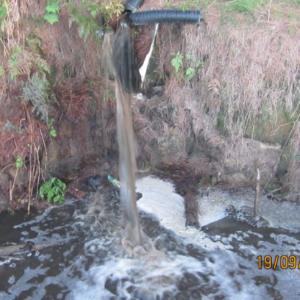 oThe contaminant discharging into the stream.