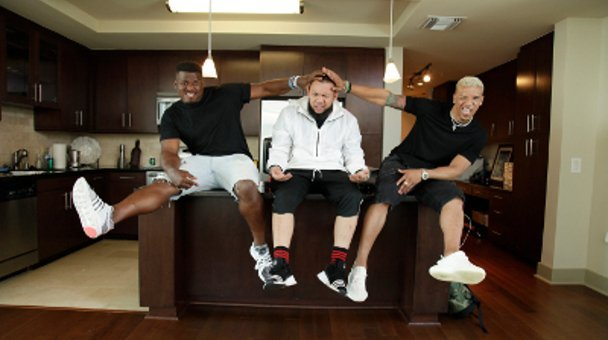 Group shot JC tha Barber footballers PJ Simien and Johnathon Stewart sitting on kitchen bench