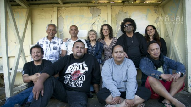 Entire cast of Once Were Warriors seated in old bus shelter - now