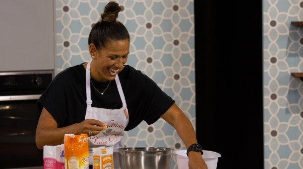 A laughing Kylie Campbell preparing her baking at the bench
