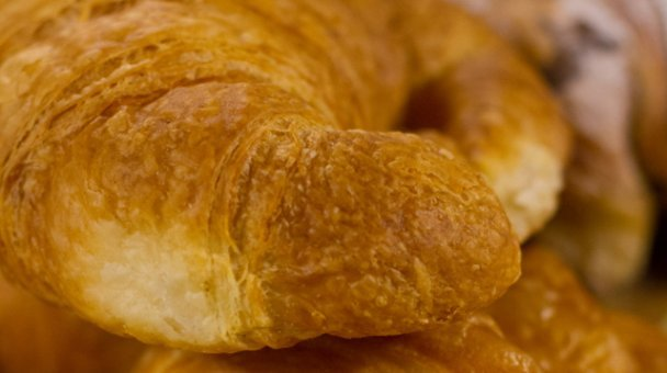 A pile of freshly baked croissants on a board
