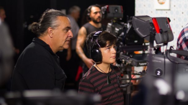 Camera-man Craig Muir oversees Niko's little brother operating a studio camera.
