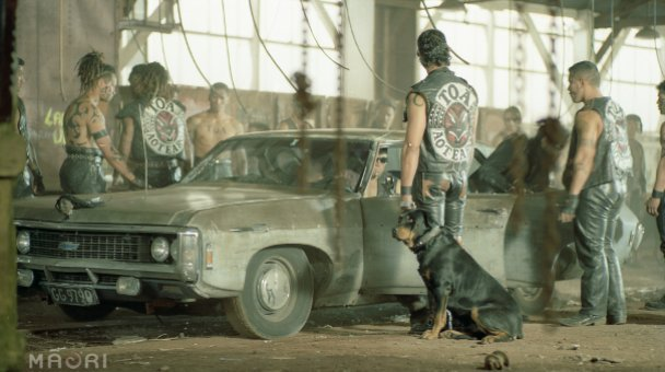 Gangsters stand around car with Rottweiler