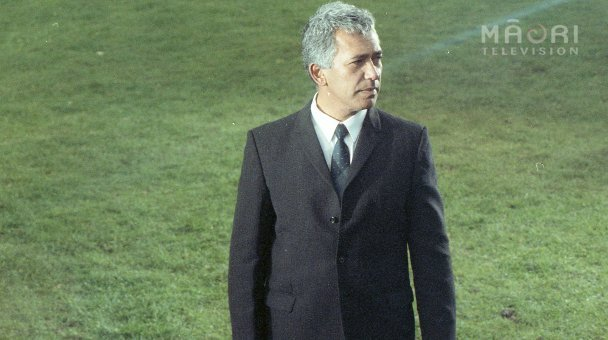 George Henare in suit standing on grass