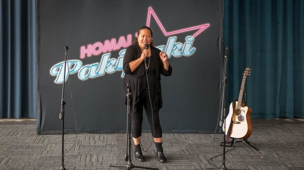 Woman singing in front of Homai signage