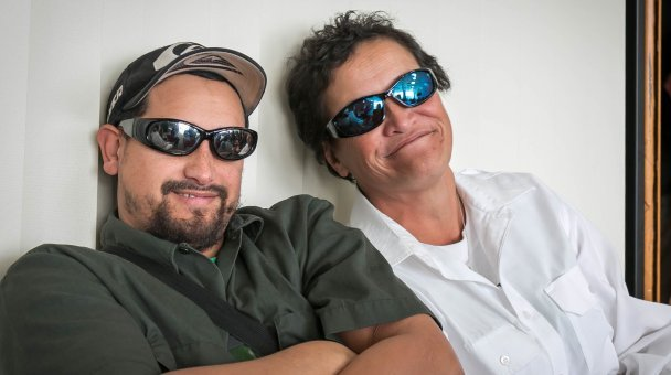 Couple of people seated wearing sunglasses smile for camera