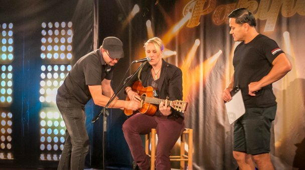 Homai crew assists lady seated with guitar ready to audition