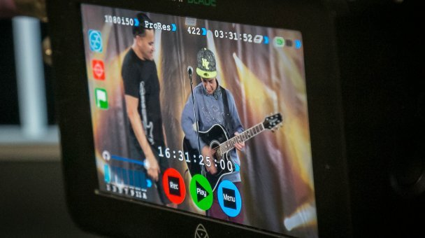 Homai staff assist young man auditioning on stage - seen through camera  screen viewer