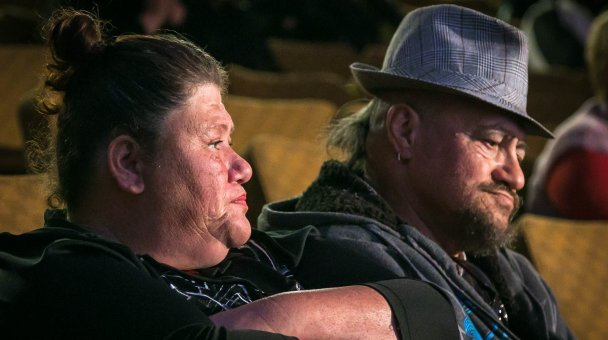 Older couple seated watching auditions