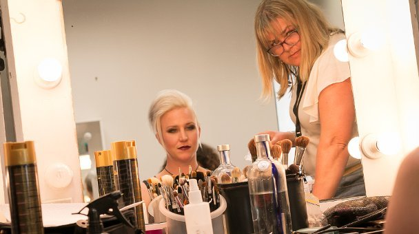 Contestant and make up artist look at selves through mirror
