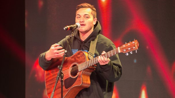 Male contestant sings with guitar on stage