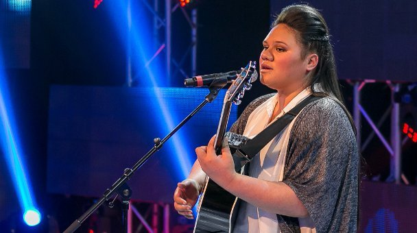 Female contestant sings on stage playing her guitar