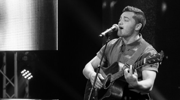 Black & white photo male contestant sings on stage with guitar