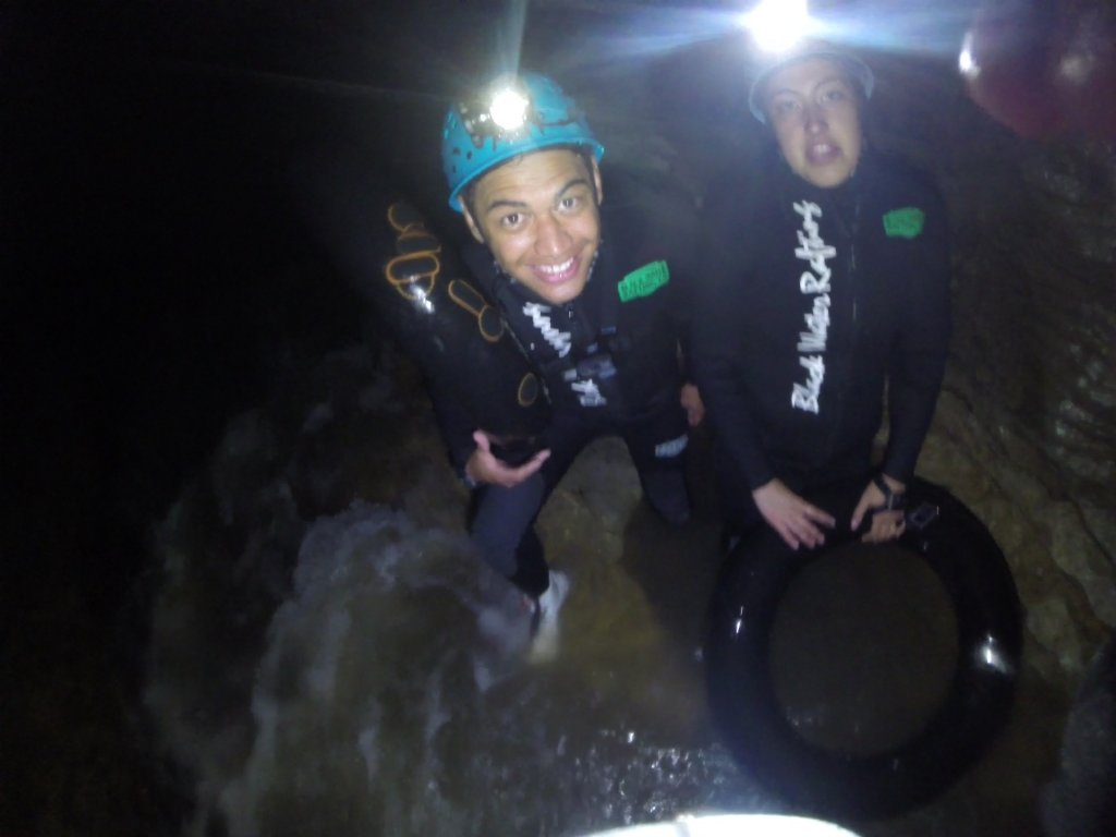 Pāia presenters in cave ready to jump - Waioira has black tyre tube in her hand