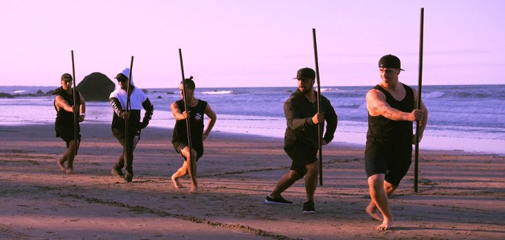 Winitana males practise mau rākau on the beach