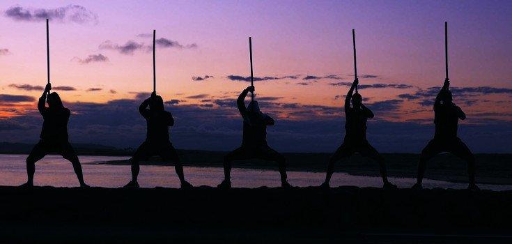 Group shot with rākau raised above head, at sunset