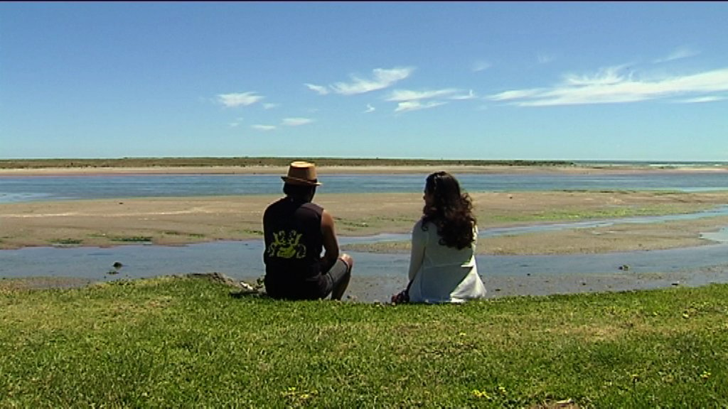 Waata and Kahurangi seated on grass looking out to the water