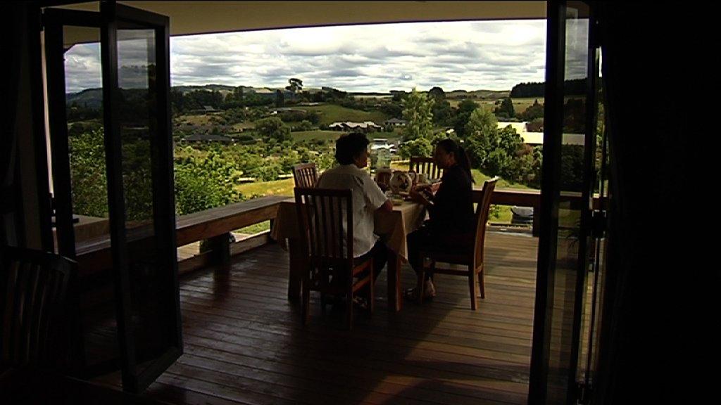 Makoha and Kahurangi seated on deck having kai