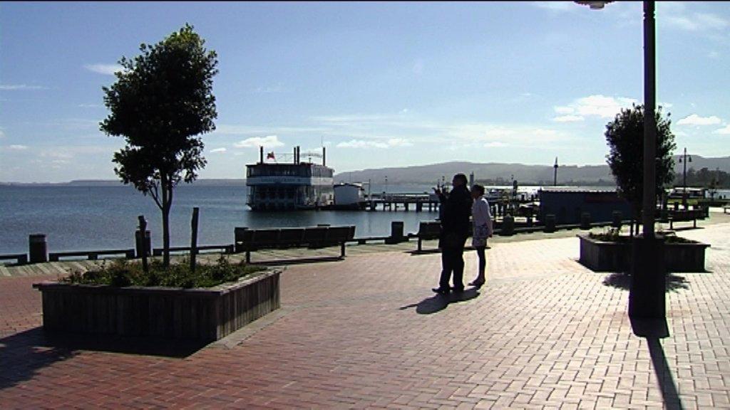 Rawiri and Kahurangi standing at Rotorua lakes edge talking looking out to the water