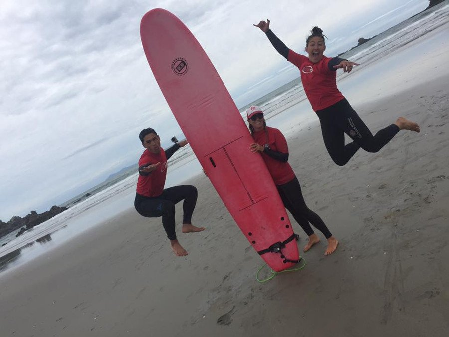 Rereahu and Waioira jump shot on beach with surf tutor holding a surfboard straight up