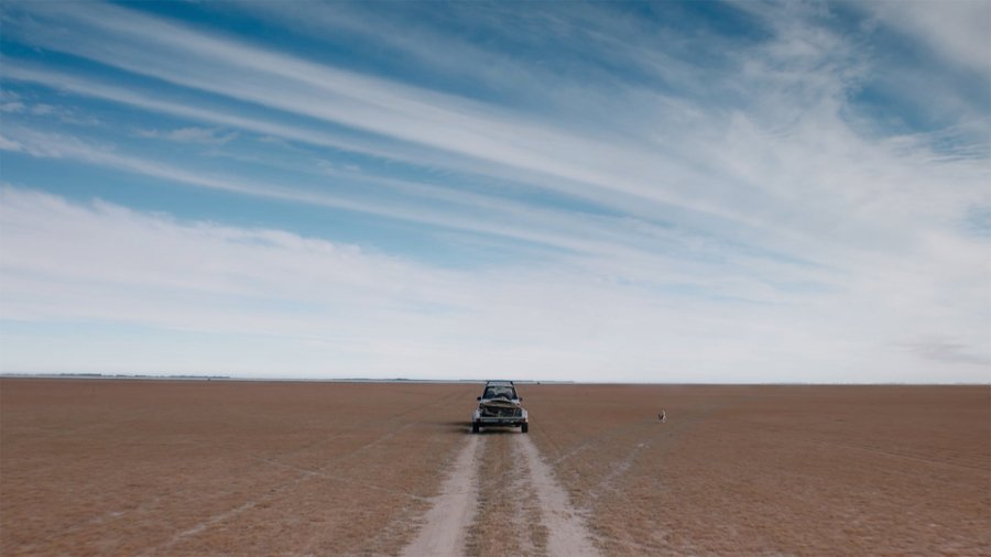 SUV with trailer travelling along a vast Southern plain