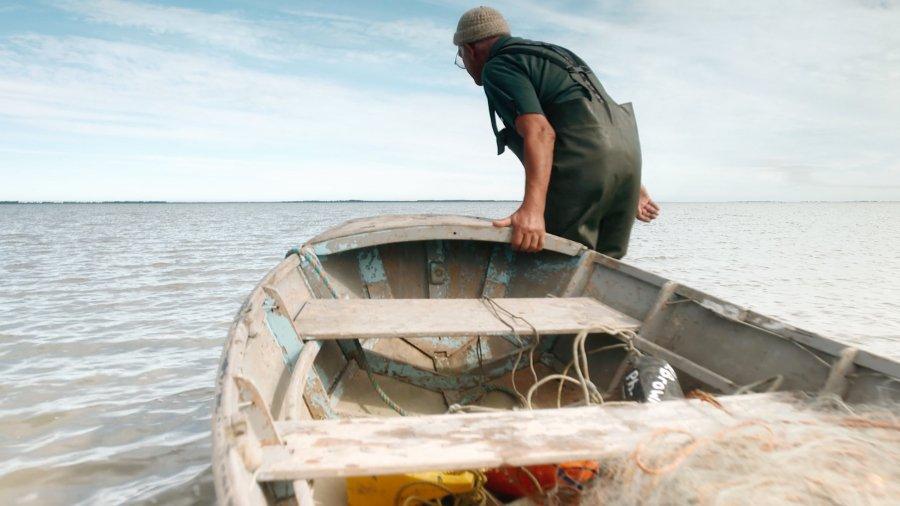 Elder Don Brown drags dinghy into ocean