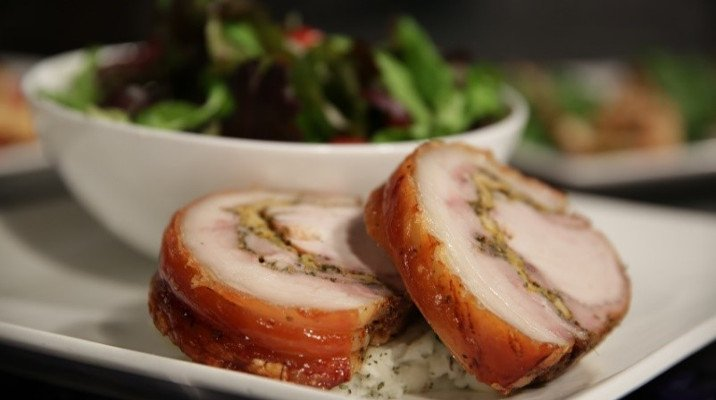 FInished Porchetta  presented on a plate with salad and mashed potatoes