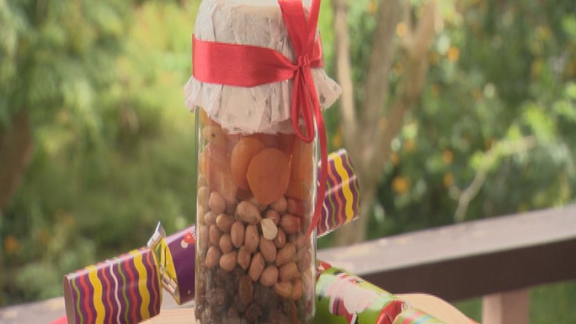 Various snacks presented in a jar on a bench