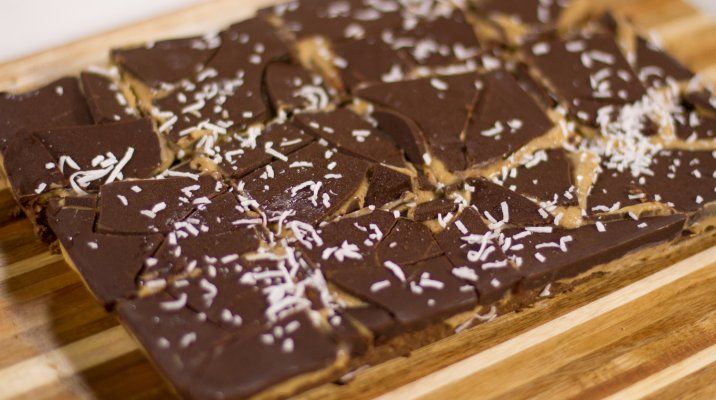 Caramel slice displayed on wooden chopping board.