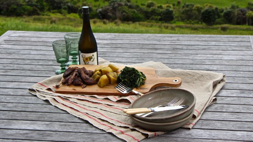 Tītī, Kūmara and Pūhā presented on a board with a bottle of wine and cutlery