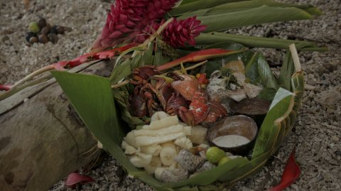Coconut Crab with Seafood platter presented in palm leaves placed in sand