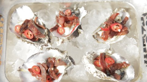 Oyster Chorizo presented in oyster half shells sitting in ice
