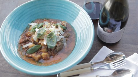Braised Lamb Shoulder presented in a bowl with cutlery and a bottle of wine