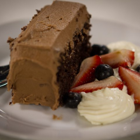 Jax Oldhams chocolate cake single portion on a plate with fruit and whipped cream on the side.